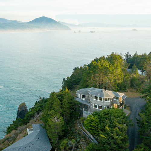 Aerial photo of a grey home overlooking the ocean