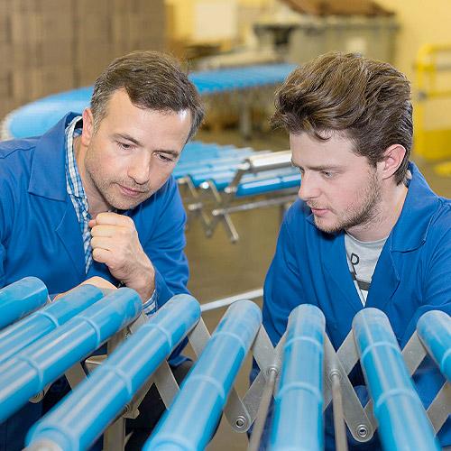 Photo of men inspecting a conveyor belt